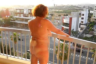 Old whore shows pussy and ass on the balcony